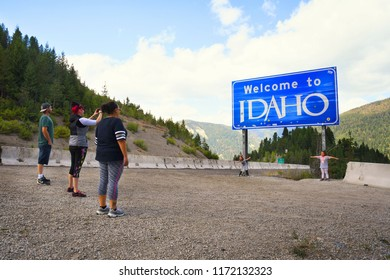 LOOKOUT PASS, IDAHO, USA - September 1, 2018: Family of five stop to take pictures at the Welcome to Idaho road sign