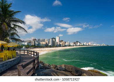 Lookout point to the Ipanema beach at Mirante do Leblon with umbrellas and chairs under coconut trees in a hot beautiful sunny summer day, blue sky, Rio de Janeiro, Brazil.