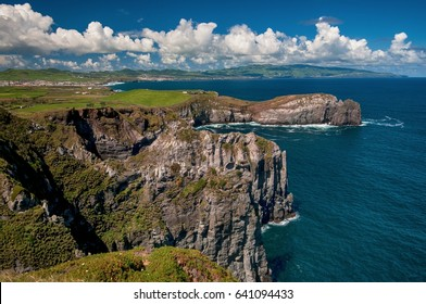 Lookout from Ponta do Cintrao at cliffs and coastline in sunny weather with beautiful cloudy blue sky, Sao Miguel Island, Azores