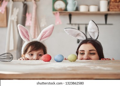 Looks at the eggs. Mother and daughter in bunny ears at easter time have some fun in the kitchen at daytime.