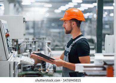 Betrachtet die Ausrüstung und macht Notizen. Industriearbeiter in Fabriken. Junge Technikerin mit orangefarbenem Hut.