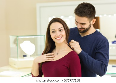 Looks good on me. Gorgeous young woman smiling while her man helping her trying on a golden necklace at the jewelry store copyspace sale consumerism luxury love anniversary shopping couples concept