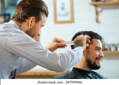 Looks great. Pleasant handsome smiling man sitting in a barber shop while professional barber making him a hair cut