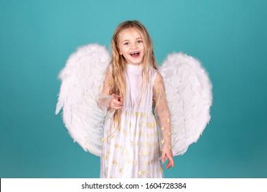 Looks like an angel. Happy angel girl over white. Christmas Cute little Angel. Beautiful little angel girl. Beautiful young girl wearing white wings