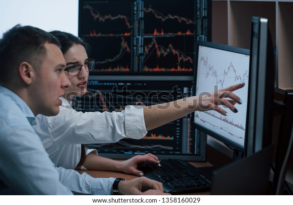 Looks like we must achieve that line. Team of stockbrokers are having a conversation in a office with multiple display screens.