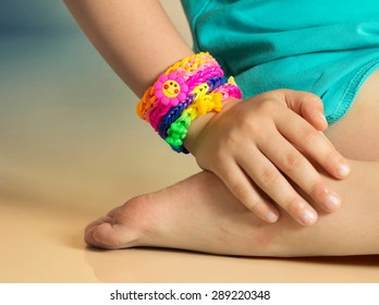 Loom bracelets on child hand close up.Rubber colorful wrist accessories.