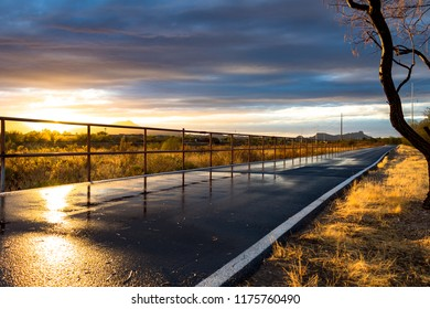 The Loop in Tucson, Arizona. A walking, running and biking path. A beautiful sunset with wet pavement picking up the light and reflecting it. The railing disappears in the distance, nice lines. 2018