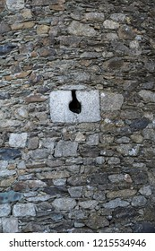 Loophole of a medieval castle. Stone wall. Spain