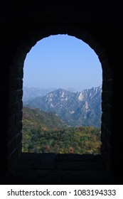 loophole. View from the window (loophole) on the great wall of China. Masonry, autumn trees.