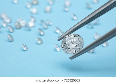 loose brilliant diamonds, one is being held by a tweezers on blue background with small diamonds