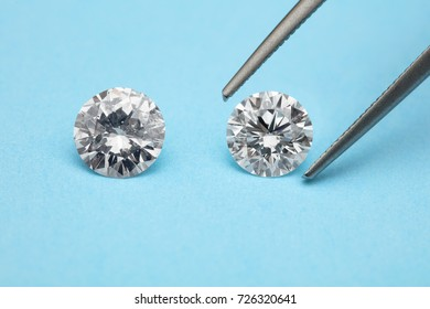 loose brilliant diamonds, one is being picked by a tweezers on blue background
