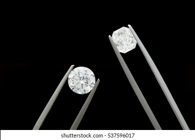 loose brilliant diamonds, round and radiant / emerald, are being held by tweezers on black background