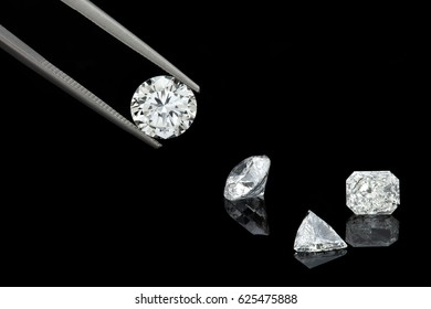 loose brilliant diamonds, round, trillion, and radiant / emerald on reflective black background one is being held by tweezers
