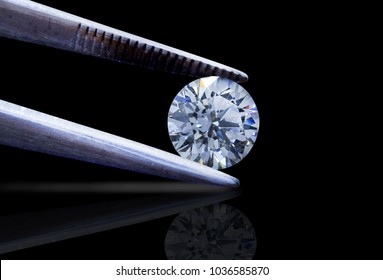 loose brilliant round diamonds is being held by tweezers on black background