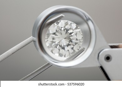 loose brilliant round diamonds is being held by tweezers and looked through a loupe