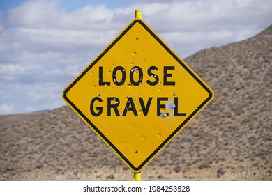 loose gravel road sign with bullet holes and out of focus desert hill and sky behind it