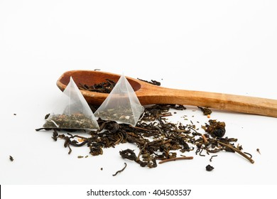 loose green tea, tea bags and a wooden spoon on a white background