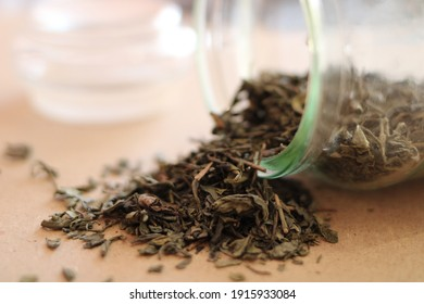 Loose green tea scattered from a glass jar