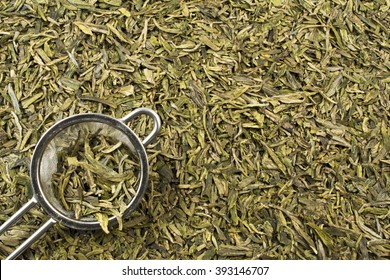 Loose Leaf Green Tea Leaves with Strainer / A tea strainer and loose leaf green tea leaves filling the frame