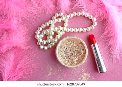 Loose make-up powder, light powder, white pearl necklace beads and boudoir in the dressing room pink retro lipstick in vintage style on a pink background and pink flamingo feathers