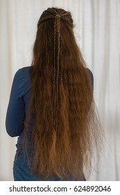Loose renaissance hairstyle for long hair. Traditional plait style modelled by girl with very long golden hair