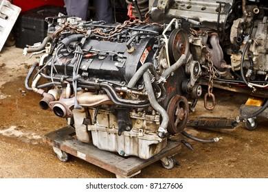 Loose vehicle engine at repair shop on wheeled cart