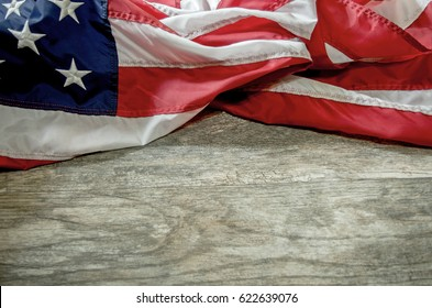 Loosely folded United States Flag on Distressed Wood Background