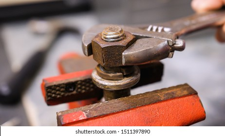 Loosening rusty nut using an adjustable crescent wrench and vise. Using spanner wrench and clamp to remove nut from bolt.