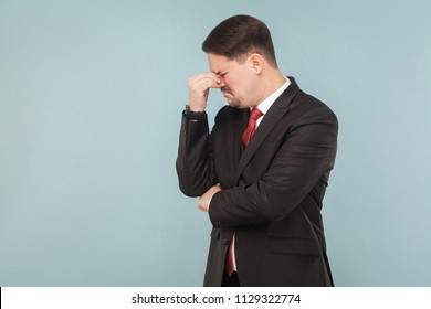 Looser businessman, crying, and hope. Need a new job and many money. indoor studio shot. isolated on light blue background. handsome businessman with black suit, red tie and mustache. side view.