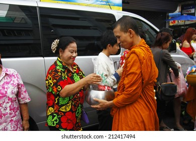 LOP BURI  AUGUST 13 : Thai people give food offerings to a Buddhist monk, Songkran Day in Thailand on August 13, 2014 in Lop Buri Thailand.