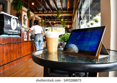 Lop Buri - Thailand, 01-09-2019: Atmosphere in the coffee shop of drinking iced coffee with news on Huawei tablet devices in the morning in a local coffee shop in Lop Buri, Thailand - Southeast Asia.