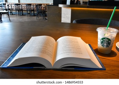 Lop Buri - Thailand, 23-08-2019: Reading and drinking coffee  Starbucks is a US coffee shop in Seattle, Washington in 1971 and has more than 30,000 locations worldwide, including Lopburi, Thai-Asia.
