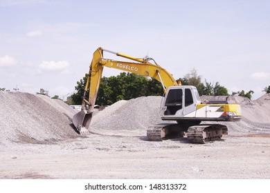 LOP BURI ,THAILAND - AUGUST 1 : Excavator  machine  working hard on  pile of gravel stone at construction site on August 1 , 2013 in Lop Buri, Thailand.