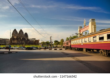 Lopburi, Thailand - August 11, 2017: The train crossing the road at the 13th century Phra Prang Sam You temple in Lopburi Province, Thailand.