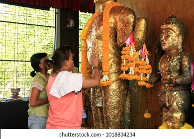 Lopburi, Thailand - Feb 11, 2010: The Thai people decorating the buddha statue with gold foil in Phra Kan Shrine, Lopburi city, on Feb 11, 2010.