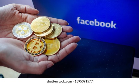 "Lopburi, Thailand/ May 12 2019:Hand holding bitcoin and all coin the background is blue  and  white text ""facebook"" . Concept  Used about Facebook news and digital money."