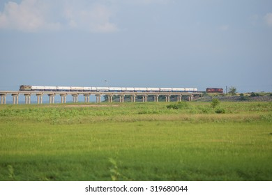 LOPBURI THAILAND - SEP 4: transportation Train on the railway cross grass field meadow at Pasuk River Dam in summer on September 4, 2015 in Lopburi, Thailand