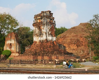 Lopburi, Thailand-February 25, 2019: the ruins of Wat Nakorn Kosa loom above a motorcyclist riding down the road.
