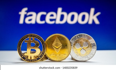 "Lopburi, Thailand/mung - May  2019:Bitcoin, ETH, XRP coin  on a white floor  The background is blue  and  white text ""facebook"" . Concept  Used about Facebook news and digital money."