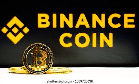 """Lopburi, Thailand/mung - May  4 2019 :Bitcoin coin on a white floor  The background is black  and  yellow text """"BINANCE COIN"""". Concept  News about  trading web binance of Chinese and digtial money."""