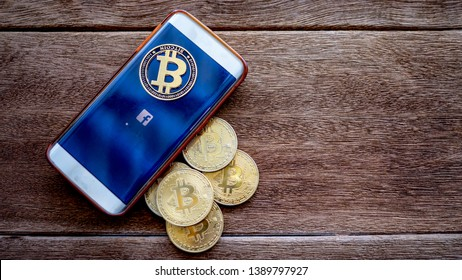 Lopburi, Thailand/mung - May 4 2019: Mobile phone the screen is symbolic F (facebook) and digital money Bitcoin coin on the wooden floor.  Concept  Used about Facebook news and digital money.