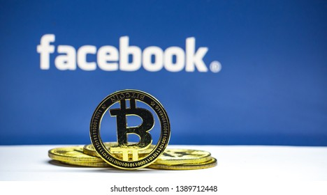 "Lopburi, Thailand/mung - May 4 2019:Bitcoin coin  on a white floor  The background is blue  and  white text ""facebook"" . Concept  Used about Facebook news and digital money."