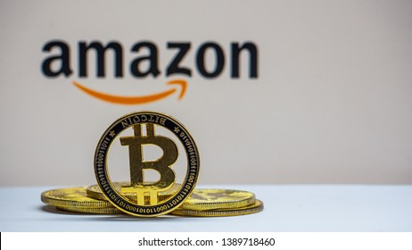 "Lopburi, Thailand/mung - May 4 2019:Bitcoin coin  on a white floor  The background is black  text ""AMAZON"" . Concept used to make stories about trading various products from Amazon with digital money."