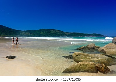 LOPES MENDES BEACH, ILHA GRANDE, RIO DE JANEIRO, BRAZIL - MARCH 22, 2009:   Beautiful shot at Lopes mendes beach, Ilha Grande, Brazil. The rocks and the ocean behind. People enjoying the beach.