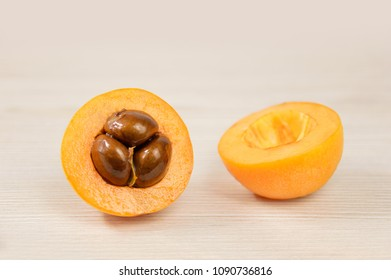 loquat cut in half and on a wooden table