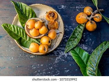 Loquat fruit. Nispero. Eriobotrya Japonica. Loquat with fresh leaves on metal background.