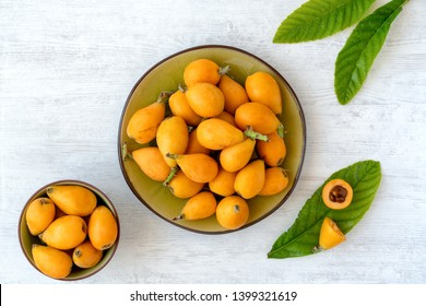 Loquat fruit. Nispero. Eriobotrya Japonica. Loquat in plate with fresh leaves on wood background