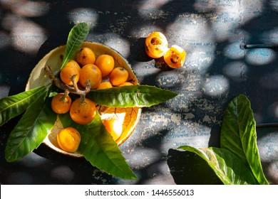 Loquat fruit. Nispero. Eriobotrya Japonica. Loquat with fresh leaves on metal background