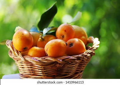 loquats on a  basket on wooden table