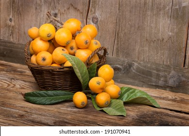 loquats on a wicker basket  on wooden background